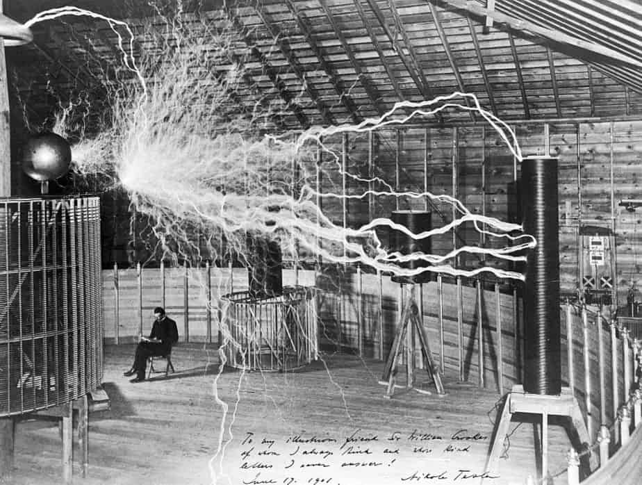 "A multiple exposure picture of Tesla sitting next to his ""magnifying transmitter"" generating millions of volts."