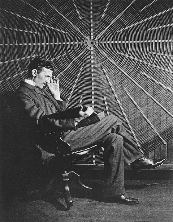 Tesla sitting in front of a spiral coil used in his wireless power experiments.